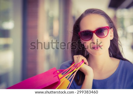 Woman looking at the the camera and wearing sunglasses