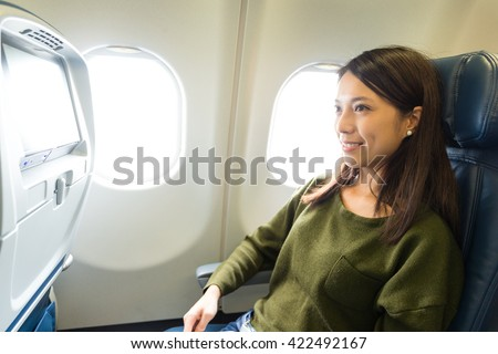 Woman looking at the window of the airplane