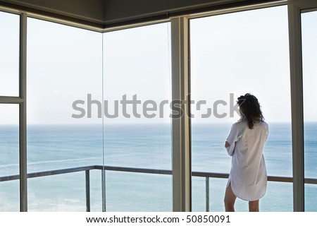 Woman looking at view, standing on balcony, back view
