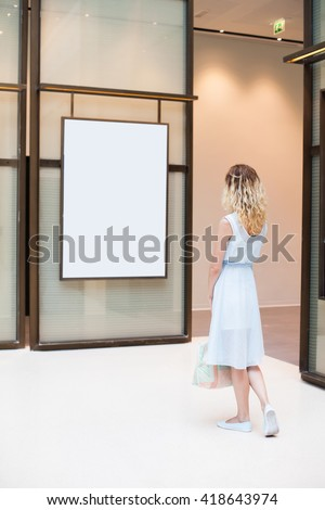woman looking at white blank poster (focus on a woman) - stock photo