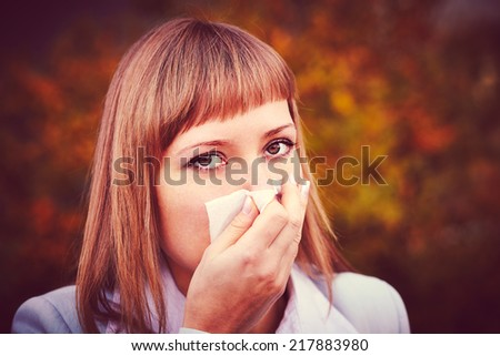 Woman looking away while blowing nose - stock photo
