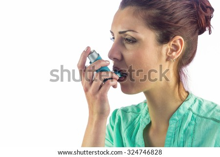 Woman looking away while using asthma inhaler against white background - stock photo