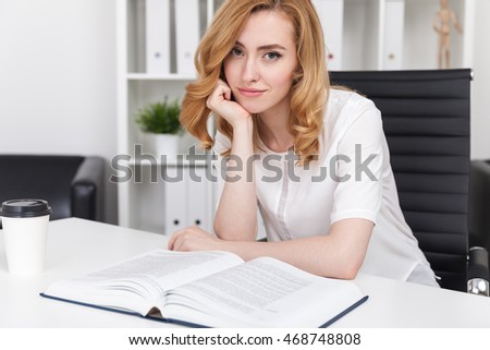 Woman looking bored sitting at her table in office with huge book. Leather armchair in background. Concept of work routine