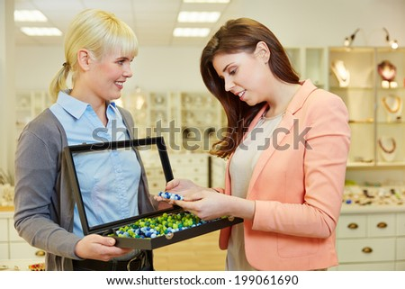 Woman looking for pearls in jewelry case in a jewelry store - stock photo