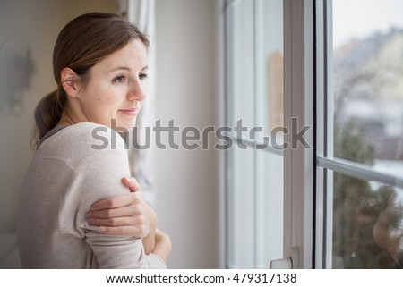 Woman looking from a window of her house on a cold and snowy winter day