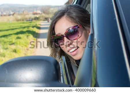 Woman looking herself at a car mirror on a roadtrip - stock photo