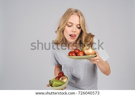 woman looking hungry at vegetables in plate on gray background