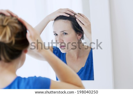 Woman looking in a mirror. - stock photo