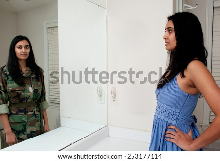 Woman looking in a mirror seeing herself as a soldier - stock photo