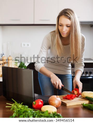 woman looking in notebook during cooking vegetables at home kitchen