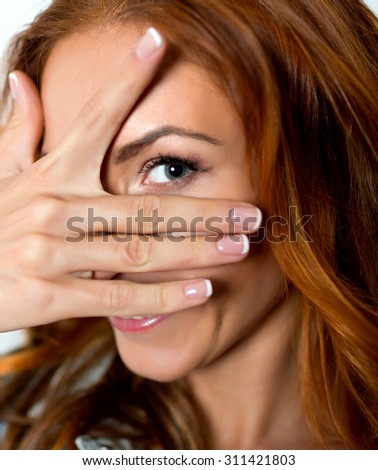 woman looking in the camera through spread fingers.she expresses positive. shot in studio