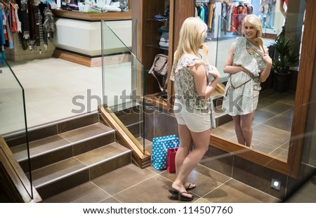 Woman looking in the mirror holding clothes in the shop - stock photo