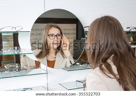 Woman looking in the mirrow while choosing glasses