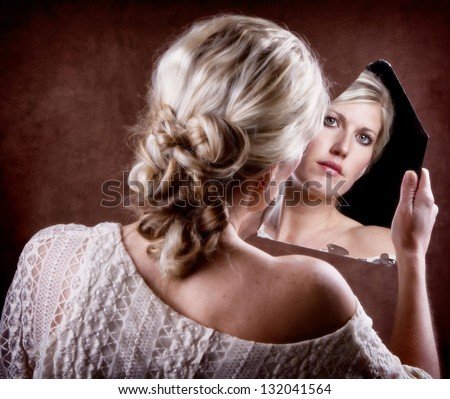 Woman looking into a broken mirror with back of head showing - stock photo