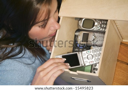 Woman looking into a drawer containing many cellphones