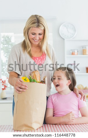 Woman looking into grocery bag beside smiling daughter in the kitchen - stock photo