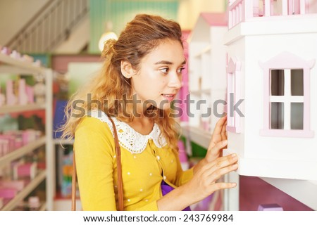 woman looking into the window of a doll house - stock photo