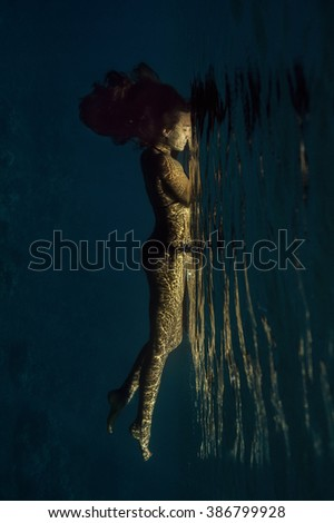 Woman looking on her mirror at water surface - stock photo