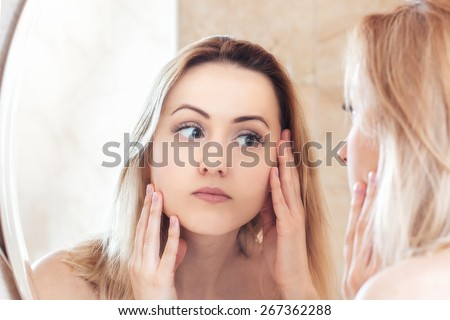 Woman looking on reflection in the mirror The beautiful young ????? with a clean fresh skin touches with a hand a cheek. - stock photo