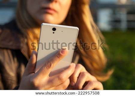 woman looking on smartphone in sunlight