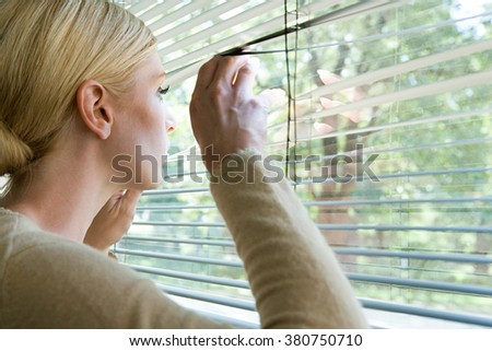 Woman looking out of blinds - stock photo