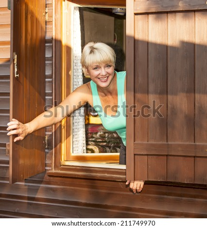 woman looking out the window of a cottage - stock photo