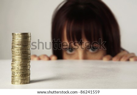 woman looking over her desk at a pile of english coins