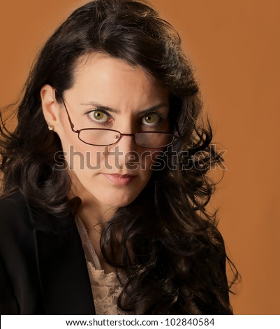 Woman looking over her glasses at you. - stock photo