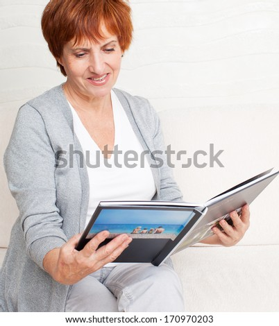 Woman looking photo book. Mature woman looking photography album