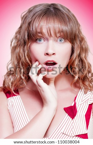 Woman looking shocked and appalled with a dropped jaw and wide eyes as she stares straight into the lens on a pink studio background with colour gradient - stock photo