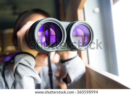 Woman looking though binoculars for birdwatching - stock photo