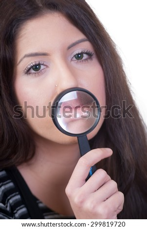 Woman looking through a magnifying lens - stock photo