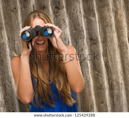 Woman Looking Through Binocular against an old rusty background - stock photo