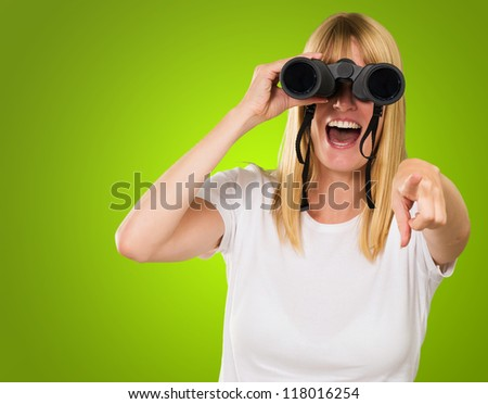 woman looking through binoculars and pointing against a green background - stock photo