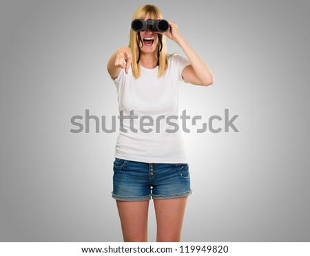 woman looking through binoculars and pointing against a grey background - stock photo