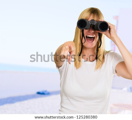 woman looking through binoculars and pointing at the beach - stock photo