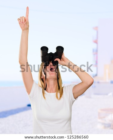 woman looking through binoculars and pointing up at the beach - stock photo