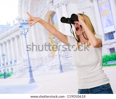 Woman Looking Through Binoculars in front of a building - stock photo