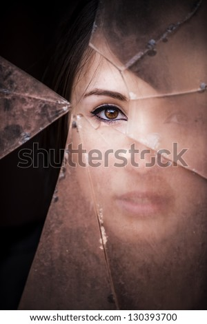 Woman looking through dirty broken glass - stock photo