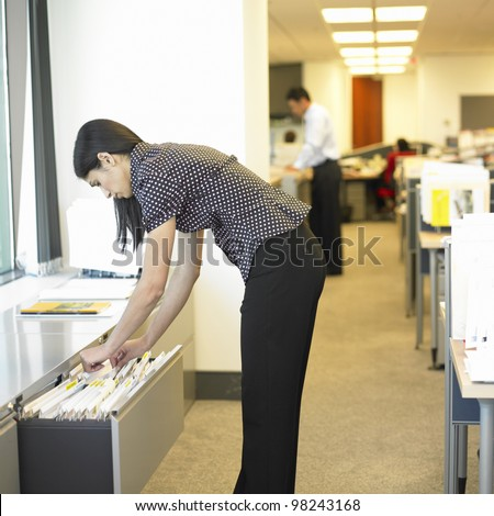 Woman looking through files in office - stock photo