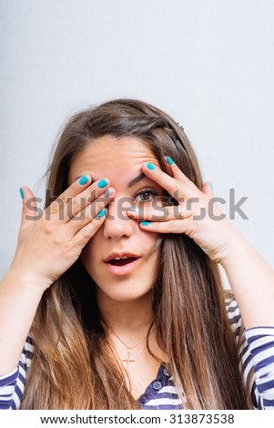 woman looking through fingers