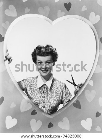 Woman looking through heart shape with scissors