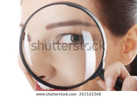 Woman looking through magnifying glass. - stock photo