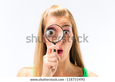 Woman looking through magnifying glass or loupe