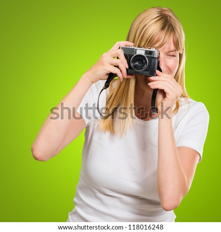 Woman Looking Through Old Camera against a green background - stock photo