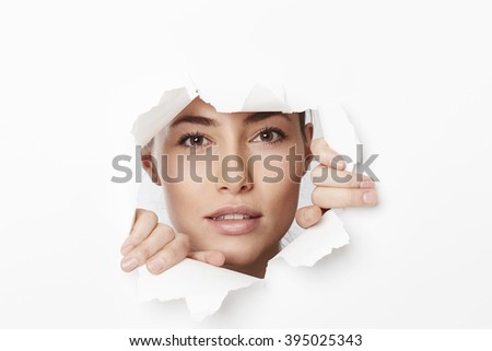 Woman looking through ripped paper