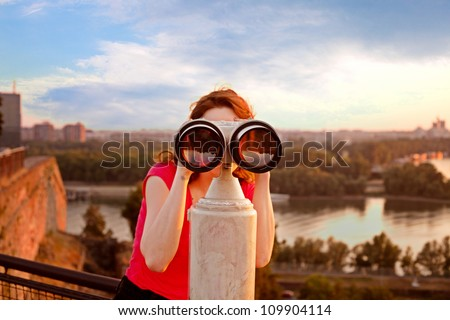 woman looking through sightseeing  binoculars on Belgrade Fortress sky, river and city in background