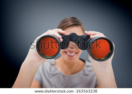 Woman looking through spyglasses against digitally generated grey vignette background - stock photo