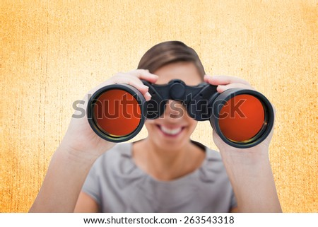 Woman looking through spyglasses against weathered surface - stock photo