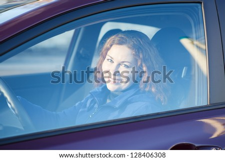 Woman looking through the car side window glass with curly hair - stock photo